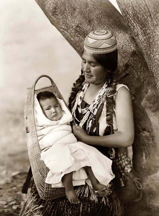 Hupa Mother and Baby in a Three-quarter Length Portrait. It was created in 1923