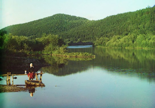 A woman is seated in a calm spot on the Sim River, part of the Volga watershed in 1910