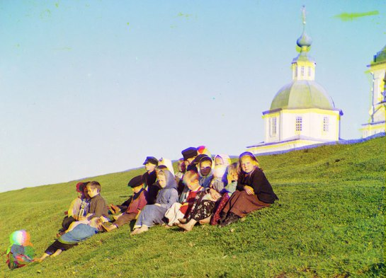 Russian children sit on the side of a hill near a church and bell tower near White Lake, in Russia, 1909